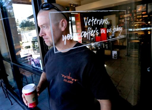 Arizona Air National Guard Lt. Col. Greg Grattop, 161st Air Refueling Wing, Phoenix Sky Harbor and Operation Enduring Freedom veteran who has served in Afghanistan, exits a Starbucks with his free coffee, Tuesday, Nov. 11, 2014 in Chandler, Ariz.