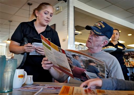 Retired U.S. Navy Vietnam veteran Larry Woodrome, orders a free lunch at Denny's, Tuesday, Nov. 11, 2014 in Gilbert, Ariz.