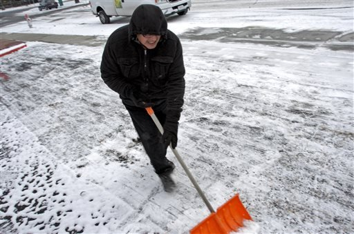 Local resident Tim Castro clears a parking lot in Billings, Mont., Tuesday, Nov. 11, 2014. Forecasters said record low temperatures were possible Wednesday morning after a cold front dropped down from Canada. (AP Photo/Matthew Brown)
