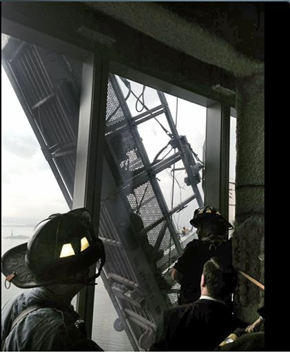This photo, from the Fire Dept. of New York Twitter page, shows a window washer's gondola as it hangs from 1 World Trade Center, in New York, Wednesday, Nov. 12, 2014.