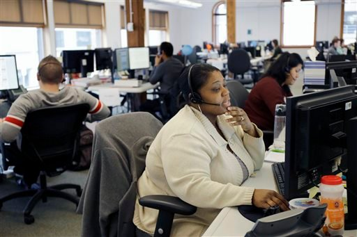 In this March 31, 2014 file photo, Loretha Cager talks with an applicant at MNSure's call center in St. Paul, Minn.