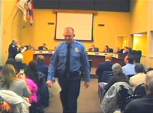 In this Feb. 11, 2014 file image from video provided by the City of Ferguson, Mo., officer Darren Wilson attends a city council meeting in Ferguson. Police identified Wilson, 28, as the police officer who shot 18-year-old Michael Brown.