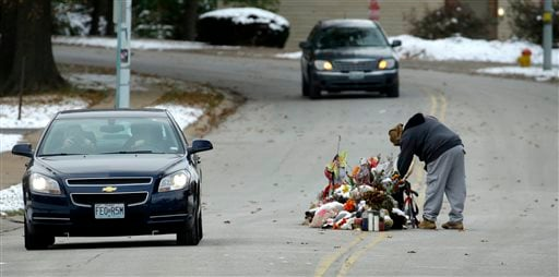 A woman looks at a memorial in the middle of the street Monday, Nov. 17, 2014, more than three months after black teen Michael Brown was shot and killed there by a white policeman in Ferguson, Mo.