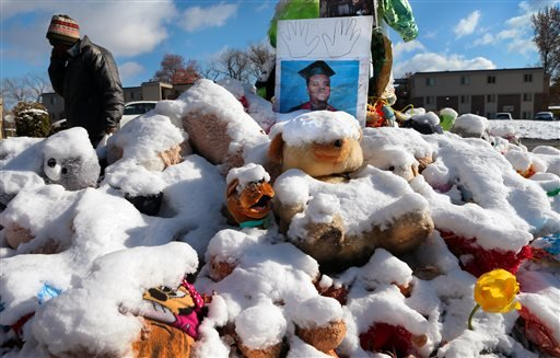 A high school graduation photo of Michael Brown rests on top of a snow-covered memorial Monday, Nov. 17, 2014, more than three months after the black teen was shot and killed nearby by a white policeman in Ferguson, Mo.