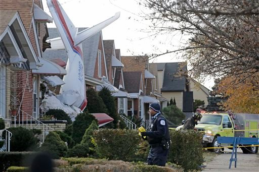Police and fire officials walk near a small twin-engine cargo plane that crashed into a home on Chicago's southwest side early Tuesday, Nov. 18, 2014. (AP)