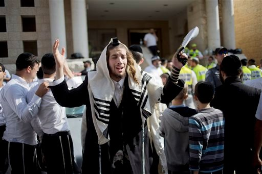 An ultra-Orthodox Jewish man prayers as Israeli rescue workers clean the scene of a shooting attack in a Synagogue in Jerusalem, Tuesday, Nov. 18, 2014. (AP)