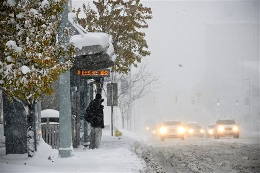A man waits in the wind and the snow for the bus along Michigan Street, Tuesday, Nov. 18, 2014 in Grand Rapids, Mich. (AP Photo/The Grand Rapids Press, Emily Rose Bennett)
