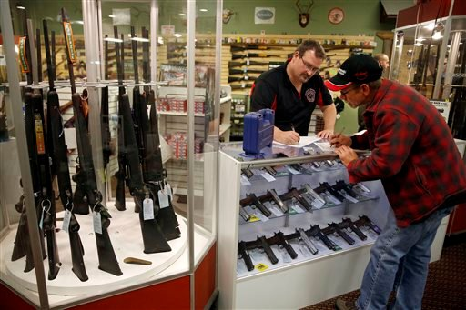 Nov. 15, 2014 photo: Steven King, left, fills out paperwork before selling a handgun to first-time gun owner Dave Benne at Metro Shooting Supplies, in Bridgeton, Mo. (AP Photo/Jeff Roberson)