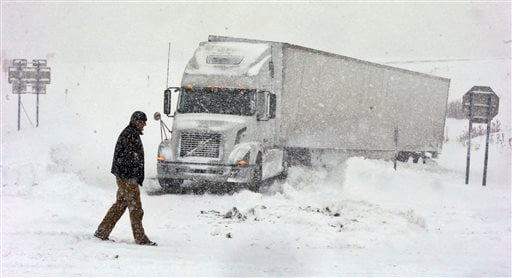 Omer Odovsc walks in front of his tractor trailer that got stuck on the 219 off ramp leading to Rt. 391 in Boston, N.Y., Tuesday, Nov. 18, 2014. (AP Photo/The Buffalo News, Harry Scull Jr.)