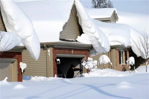 Snowdrifts create a beautiful setting as a man tries to dig out his driveway on Bowen Rd in Lancaster, N.Y. Nov. 19, 2014. A lake-effect snow storm dumped over five feet of snow in areas across Western New York. (AP photo/Gary Wiepert)