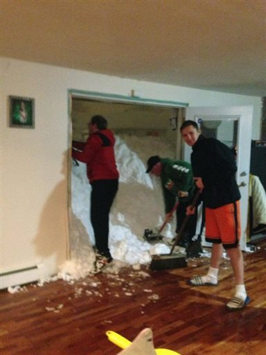 In this photo provided by Chrissy Hazard, Mark Hazard, his son Jason and Bryan Juda shovel out the snow from the home of Chrissy Hazard on Nov. 18, 2014 in Cheektowaga, N.Y. (AP Photo/Courtesy of Chrissy Hazard )