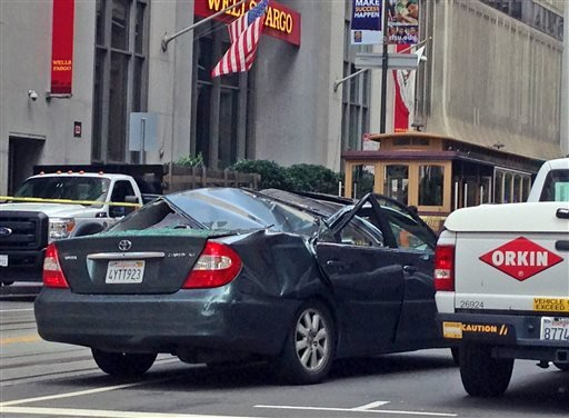 A Toyota Camry has a caved in roof after a window washer fell at least 11 stories onto the moving vehicle in San Francisco, Friday, Nov. 21, 2014. Police say the San Francisco window washer survived the falling on Friday. (AP Photo/Lisa Leff)