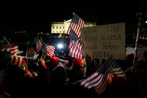 Rally participants wave American flags and signs as they gather in front of the White House in Washington, Thursday, Nov. 20, 2014. (AP)