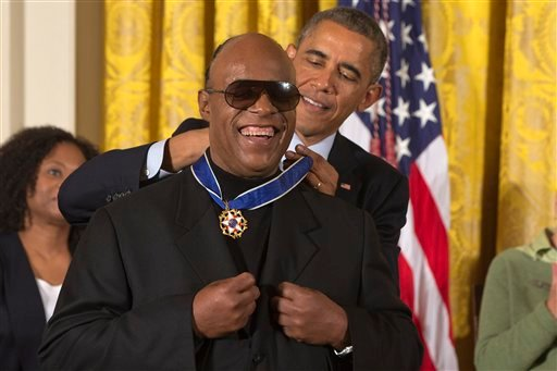 Musician Stevie Wonder celebrates as President Barack Obama awards him the Presidential Medal of Freedom, Monday, Nov. 24, 2014, during a ceremony in the East Room of the White House in Washington.