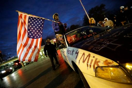 Gina Gowdy holds an upside-down American flag Monday, Nov. 24, 2014, in Ferguson, Mo., more than three months after an unarmed black 18-year-old man was shot and killed there by a white policeman. (AP)