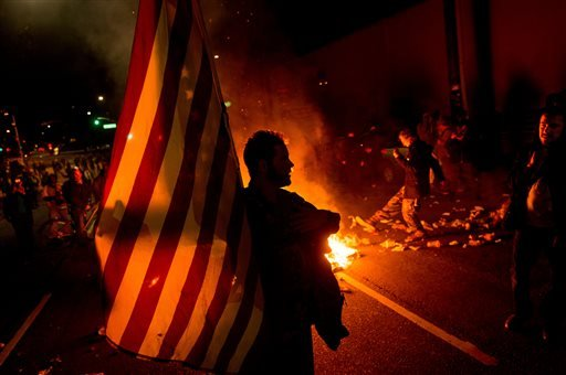 James Cartmill holds an American flag while protesting in Oakland, Calif. Nov. 24, 2014, after the announcement that a grand jury decided not to indict Ferguson police officer Darren Wilson. (AP Photo/Noah Berger)