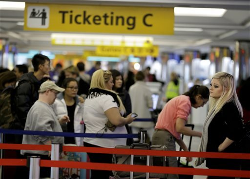 Travelers wait in lines to check in at LaGuardia Airport in New York, Tuesday, Nov. 25, 2014. (AP Photo/Seth Wenig)