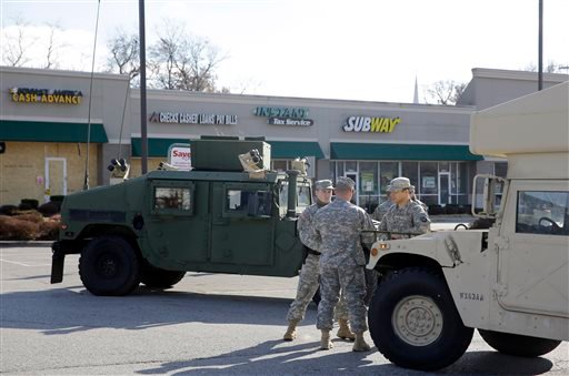 Members of the Missouri National Guard stand in a parking lot of Tuesday, Nov. 25, 2014, in Dellwood, Mo. (AP Photo/Jeff Roberson)