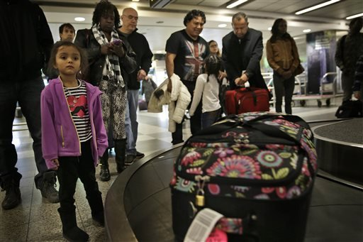 Travelers wait to claim their baggage at LaGuardia Airport in New York, Tuesday, Nov. 25, 2014. (AP Photo/Seth Wenig)