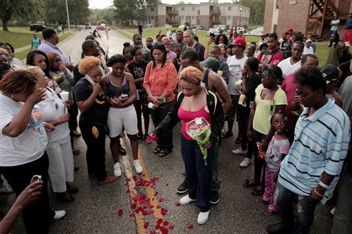 FILE- In this Aug. 9, 2014, file photo, Lesley McSpadden, center, drops rose petals on the blood stains from her 18-year-old son Michael Brown who was shot and killed a police officer in Ferguson, Mo., Aug. 9. (AP)