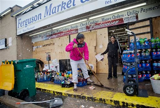 Anjana Patel cleans up the damage from Monday's riots at her store, Ferguson Market and Liquor, Wednesday, Nov. 26, 2014, in Ferguson, Mo. (AP)