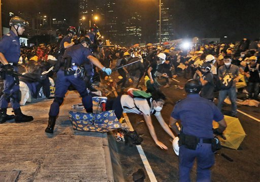 Police officers throw a pro-democracy protester on the main road outside government headquarters in Hong Kong Sunday, Nov. 30, 2014. Hundreds of pro-democracy protesters faced off with Hong Kong police late Sunday, stepping up their movement for genuine d