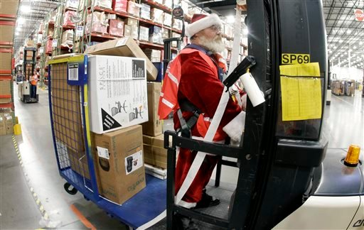 Glenn Wright, dressed in a Santa Claus costume, moves items at the Amazon fulfillment center on Monday, Dec. 1, 2014, in Lebanon, Tenn. (AP)