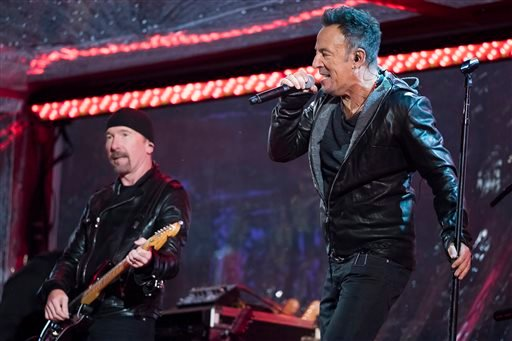 The Edge and Bruce Springsteen perform during the World AIDS Day (RED) concert in Times Square on Monday, Dec. 1, 2014 in New York.