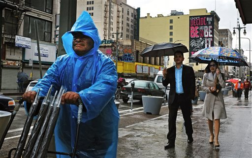 An umbrella vendor makes his way along a soggy city street in downtown Los Angeles on Wednesday, Dec. 3, 2014. (AP)