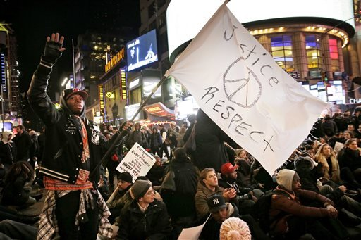 Protesters block traffic in Times Square during a march in response to the grand jury's decision in the Eric Garner case in New York, Wednesday, Dec. 3, 2014. (AP)