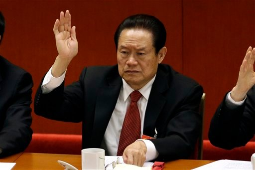 In this Wednesday Nov. 14, 2012 file photo, Zhou Yongkang, the then Chinese Communist Party Politburo Standing Committee member in charge of security, raises his hand to show approval for a work report during the closing ceremony for the 18th Communist Pa