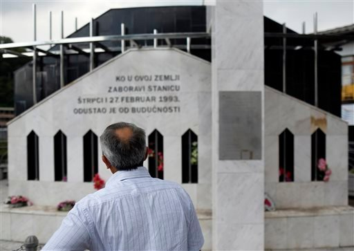 In this photo taken Wednesday, July 16, 2014, Nail Kaljevic stands in front of the monument dedicated to victims of the Strpci abduction in Prijepolje, Serbia. Investigators in Serbia and Bosnia now say they have finally cracked the case which was systema