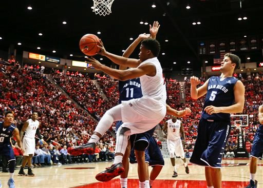 San Diego State guard Kevin Zabo is airborne while looking for someone to pass to as he drives the baseline against San Diego guard Marcus Harris in the first half of an NCAA college basketball game Thursday, Dec. 4, 2014, in San Diego. (AP Photo)