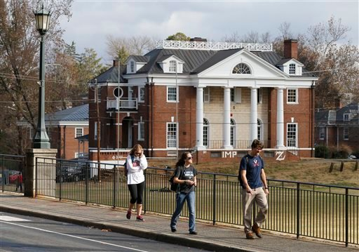 University of Virginia students walk to campus past the Phi Kappa Psi fraternity house at the University of Virginia in Charlottesville, Va., Monday, Nov. 24, 2014. The university has suspended activities at all campus fraternal organizations amid an inve