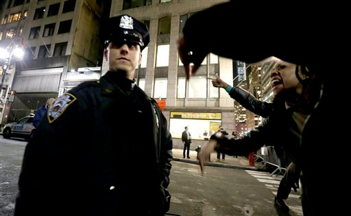 A woman, right, yells at a New York City Police officer during a protest after it was announced that the police officer involved in the death of Eric Garner is not being indicted, Wednesday, Dec. 3, 2014, in New York. A grand jury cleared the white New Yo