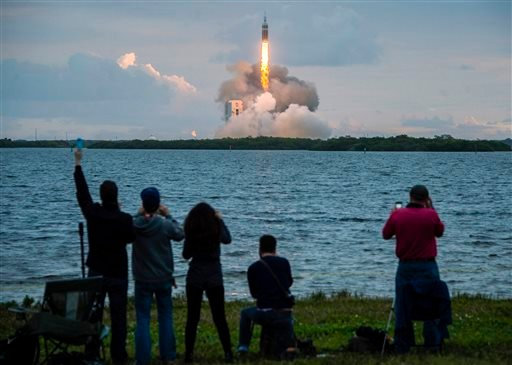 Spectators cheer as the United Launch Alliance Delta 4-Heavy rocket, with NASA's Orion spacecraft mounted atop, lifts off from the Cape Canaveral Air Force Station, Friday, Dec. 5, 2014, in Cape Canaveral, Fla. (AP Photo/Houston Chronicle, Smiley N. Pool)