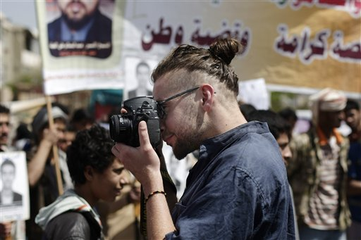 In this Tuesday, April 16, 2013 photo, Luke Somers, 33, an American photojournalist who was kidnapped over a year ago by al-Qaida, uses a camera during a demonstration demanding the release of Yemeni detainees in Guantanamo Bay prison in front of the U.S.