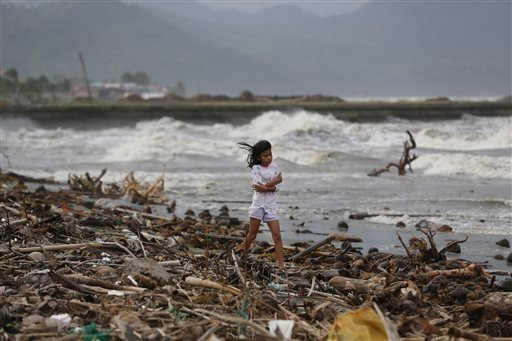 A girl walks along the shore as strong waves from Typhoon Hagupit hit Atimonan, Quezon province, eastern Philippines on Saturday, Dec. 6, 2014. Haunted by Typhoon Haiyan's massive devastation last year, more than 600,000 people fled Philippine villages an