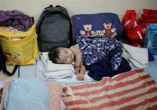 Filipino Jonrey Pawang sleeps beside his family's belongings as they take refuge at a school used as an evacuation center, in Legazpi, Albay province, eastern Philippines Saturday, Dec. 6, 2014. Typhoon Hagupit slammed into the central Philippines' east c