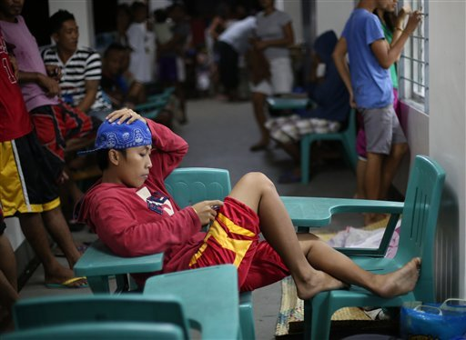 A Filipino woman uses her mobile phone at a school as they prepare for Typhoon Hagupit in Legazpi, Albay province, eastern Philippines Saturday, Dec. 6, 2014. Typhoon Hagupit slammed into the central Philippines' east coast late Saturday, knocking out pow