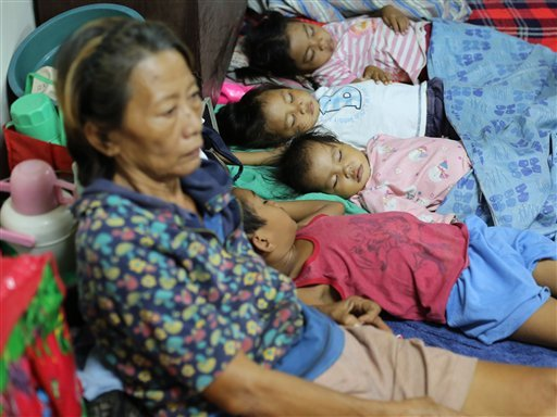 Filipino children sleep as families seek refuge at a school used as an evacuation center as they prepare for Typhoon Hagupit in Legazpi, Albay province, eastern Philippines, Saturday, Dec. 6, 2014. Typhoon Hagupit slammed into the central Philippines' eas