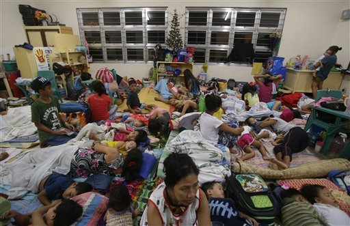 Filipino families seek refuge at a school used as an evacuation center as they prepare for Typhoon Hagupit in Legazpi, Albay province, eastern Philippines Saturday, Dec. 6, 2014. Typhoon Hagupit slammed into the central Philippines' east coast late Saturd
