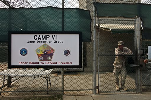 In this file photo taken Tuesday May 12, 2009 and reviewed by the U.S. military, a soldier stands guard at the front gate entrance to Guantanamo's Camp 6 maximum-security detention facility, at Guantanamo Bay U.S. Naval Base, Cuba. The U.S. government sai