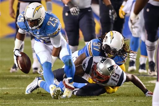 San Diego Chargers defensive back Darrell Stuckey picks up a fumble before scoring a touchdown against the New England Patriots during the first half in an NFL football game Sunday, Dec. 7, 2014, in San Diego.
