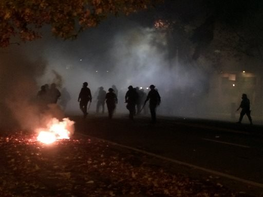 In this photo provided by Tay Nitta, police in riot gear patrol a street in Berkeley, Calif. amid smoke and tear gas after a protest over police killings turned violent, early Sunday, Dec. 7, 2014. Two officers were injured in the protests, with protester