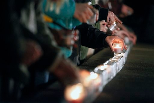 Charlottesville High School students light candles along the stage during a vigil in support of sexual-assault victims held at the McIntire Amphitheatre at the University of Virginia Dec. 5, 2014. (AP Photo/The Daily Progress, Ryan M. Kelly)