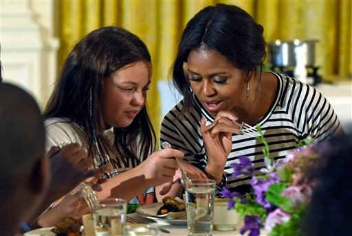 In this Oct. 14, 2014 file photo, first lady Michelle Obama and a student look over their plates as they eat lunch in the East Room of the White House in Washington following the annual fall harvest of the White House Kitchen Garden. (AP)