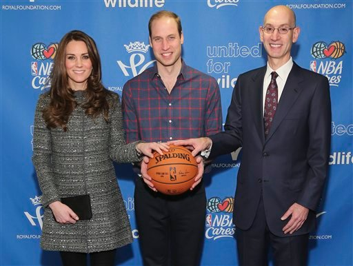 Britain's Prince William, the Duke of Cambridge, center, and Kate, the Duchess of Cambridge, left, pose for a photo with NBA Commissioner Adam Silverwhile attending an NBA basketball game between the Cleveland Cavaliers and Brooklyn Nets. (AP)