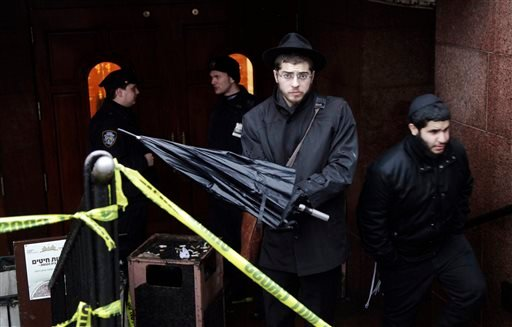 A member of the Lubavitch community, center, leaves the Chabad-Lubavitch Hasidic headquarters guarded by members of the New York Police Department, left, Tuesday, Dec. 9, 2014, in New York. A knife-wielding man stabbed an Israeli student inside the Brookl