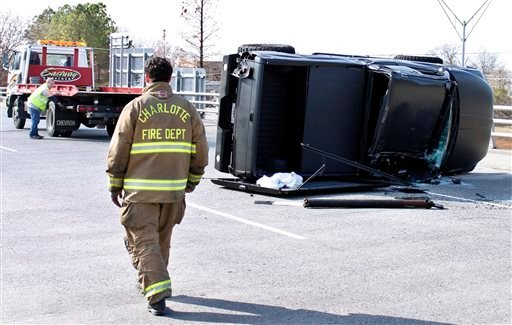 A towing-operator works to upright the damaged truck driven by Carolina Panthers quarterback Cam Newton after the quarterback was involved in an accident, Tuesday, Dec. 9, 2014, in Charlotte, N.C.